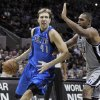 Photo - Dallas Mavericks' Dirk Nowitzki, left, of Germany, drives around San Antonio Spurs' Boris Diaw, of France, during the second half of an NBA basketball game, Sunday, Dec. 23, 2012, in San Antonio. San Antonio won 129-91. (AP Photo/Darren Abate)