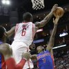 Detroit Pistons guard Brandon Jennings (7) has his shot blocked by Houston Rockets\' Terrence Jones (6) during the first half of an NBA basketball game, Saturday, March 1, 2014, in Houston. (AP Photo/Bob Levey)