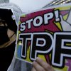 Photo - A protester holds a placard during a rally against the Trans-Pacific Partnership (TPP) in Tokyo, Tuesday, April 22, 2014. In Japan and elsewhere, there are concerns over making politically difficult market-opening concessions without reassurance that Obama will have the