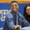 Photo - Huntington Prep basketball player Andrew Wiggins smiles along side his mother Marita Payne-Wiggins, right, as he announces his commitment to the University of Kansas during a ceremony, Tuesday, May 14, 2013, at St. Joseph High School in Huntington W.Va. The Canadian star, a top prospect, averaged 23.4 points and 11.2 rebounds per game this season for West Virginia's Huntington Prep. (AP Photo/The Herald-Dispatch, Sholten Singer)