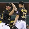Photo - Pittsburgh Pirates' Travis Snider, left, celebrates with relief pitcher Mark Melancon (35) after the Pirates' 4-2 win over the Colorado Rockies in a baseball game in Pittsburgh on Friday, July 18, 2014. (AP Photo/Gene J. Puskar)