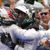 Mercedes driver Lewis Hamilton, left, of Britain is congratulated by teammate and second placed Nico Rosberg of Germany after winning the Malaysian Formula One Grand Prix at Sepang International Circuit in Sepang, Malaysia, Sunday, March 30, 2014. (AP Photo/Vincent Thian)