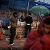Indians stand wrapped in warm clothes near a tea stall, as a woman keeps herself warm next to a small bonfire on a footpath on a cold morning in New Delhi, India, Wednesday, Jan. 9, 2013. North India continues to face below average weather conditions with dense fog affecting flights and trains. More than 100 people have died of exposure as northern India deals with historically cold temperatures. (AP Photo/Altaf Qadri)