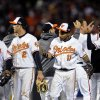 Baltimore Orioles\' Nate McLouth, from left, J.J. Hardy, Robert Andino and Manny Machado high-five teammates after Game 2 of the American League division baseball series against the New York Yankees on Monday, Oct. 8, 2012, in Baltimore. Baltimore won 3-2. (AP Photo/Nick Wass)