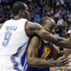 Oklahoma City Thunder forward Serge Ibaka (9) fouls Golden State Warriors forward Carl Landry (7) as he drives to the basket in the second quarter of an NBA basketball game in Oklahoma City, Sunday, Nov. 18, 2012. (AP Photo/Sue Ogrocki)