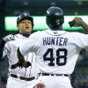 Photo - Detroit Tigers' Miguel Cabrera is congratulated by teammate Torii Hunter after hitting a two-run home run during the first inning of a baseball game against the Minnesota Twins in Detroit, Thursday, May 23, 2013. (AP Photo/Carlos Osorio)