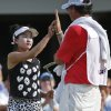 Photo - Lucy Li, left, gets a high-five from her caddie, Bryan Bush, right, after finishing her round during the second round of the U.S. Women's Open golf tournament in Pinehurst, N.C., Friday, June 20, 2014. (AP Photo/John Bazemore)
