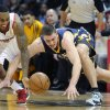 Photo - Atlanta Hawks point guard Jeff Teague, left, and Indiana Pacers power forward Tyler Hansbrough, right, vie for a loose ball during the first half of an NBA basketball game on Saturday, Dec. 29, 2012, at Philips Arena in Atlanta. (AP Photo/John Amis)