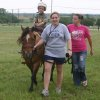 Sensory Exploration camper Nate Oakley receives tactile, smell and movement stimulation while riding on American Quarter Horse Poco Highbrow Jessie, a.k.a. Cody. Oakley was one of 18 area children participating in the Sensory Exploration day camp held at the J. D. McCarty Center. Leading Cody is McCarty Center occupational therapy assistant Mikki Patten. Acting as Nate's side walker is day camp volunteer Amanda Snow. Community Photo By: Greg Gaston Submitted By: Greg,