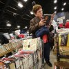 Linda McCormack spends a minute scanning the pages of a book to decide if she wants to add it to her shopping cart, already full of books. McCormack drove to the sale from Granite. She said her first sale was five years ago and she knew then she was