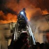 Photo - Firefighters battle a fire that tore through three townhouses on New York City's Staten Island early Thursday, June 5, 2014. At least 34 people were injured, including two young children who were tossed out of a smoke-filled second-floor window into the arms of neighbors below, authorities and witnesses said. (AP Photo/Staten Island Advance, Ryan Lavis)
