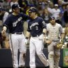Colorado Rockies catcher Michael McKenry watches as Milwaukee Brewers\' Mark Reynolds (7) congratulates Scooter Gennett (2) after Gennett\'s two-run home run during the eighth inning of a baseball game Thursday, June 26, 2014, in Milwaukee. (AP Photo/Morry Gash)