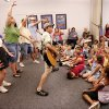 Mr. Stinky Feet and the Hiccups, with guitarist Jim Cosgrove, playing the guitar, entertain children at the Bethany Public Library Tuesday afternoon, July 21, 2009. Adults behind Cosgrove were called to the stage area to lead the children in hand signals for the Unicorn song. Photo by Jim Beckel, The Oklahoman