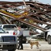 A police officer offers directions to a driver leaving this heavily damaged supply yard for Cactus Drilling Company on State Highway 66 in El Reno on Saturday, June 1, 2013. Employee David Stottemyre was working in the lot when the tornado took aim at the plant. Stottemyre ran inside the large supply storage building and took shelter as the tornado passed over, leaving the building in a twisted pile of steel and metal. He was not injured. Photo by Jim Beckel, The Oklahoman.