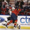 Photo - Boston Bruins' Johnny Boychuk, center left, and Florida Panthers' Krys Barch (21) slam into the wall during the second period of an NHL hockey game in Sunrise, Fla., Sunday, March 9, 2014. (AP Photo/J Pat Carter)