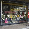 Photo - People look at flowers laid in memory of Willem Grootscholten, a victim of flight MH17, who worked for 12 years as a bouncer at the cannabis-selling cafe Andersom in Utrecht, Netherlands, Sunday, July 20, 2014. An attack on a Malaysian jetliner shot down over Ukraine on Thursday killed 298 people from nearly a dozen nations, more than half being Dutch. Worshippers at church services across the Netherlands prayed Sunday for the victims of the Ukraine air disaster and their next of kin, as anger built over the separatist rebels' hindering of the investigation into the downing of Malaysia Airlines Flight 17. (AP Photo/Mike Corder)
