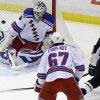 Photo - Pittsburgh Penguins' Jussi Jokinen, right, lifts a shot over New York Rangers goalie Henrik Lundqvist, top, in the first period of an NHL hockey game in Pittsburgh, Friday, Jan. 3, 2014. (AP Photo/Gene J. Puskar)