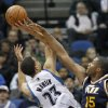 Photo - Utah Jazz center Derrick Favors (15) swats away a shot-attempt by Minnesota Timberwolves guard Kevin Martin (23) during the second quarter of an NBA basketball game in Minneapolis, Wednesday, April 16, 2014. (AP Photo/Ann Heisenfelt)