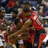 Photo - Toronto Raptors forward Amir Johnson (15)  and guard DeMar DeRozan (10) combine on Washington Wizards guard Bradley Beal (3) in the first half of an NBA basketball game, Friday, Jan. 3, 2014, in Washington. (AP Photo/Alex Brandon)