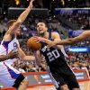 Photo - San Antonio Spurs guard Manu Ginobili (20), of Argentina, drives on Los Angeles Clippers forward Blake Griffin. left center,  center DeAndre Jordan, left, and forward Jared Dudle, right, as he goes to the basket in the first half of a NBA basketball game, Tuesday, Feb. 18, 2014, in Los Angeles.(AP Photo/Gus Ruelas)