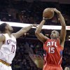 Photo - Atlanta Hawks' Al Horford (15) shoots over Cleveland Cavaliers' Tristan Thompson (13) during the first quarter of an NBA basketball game Thursday, Dec. 26, 2013, in Cleveland. (AP Photo/Tony Dejak)