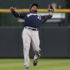 Photo - Milwaukee Brewers second baseman Rickie Weeks pulls in a pop fly off the bat of Colorado Rockies' Justin Morneau in the third inning of a baseball game in Denver on Sunday, June 22, 2014. (AP Photo/David Zalubowski)