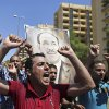 """Photo - Iraqis chant pro-government slogans and display placards bearing a picture of embattled Prime Minister Nouri al-Maliki during a demonstration in Baghdad, Iraq, Monday, Aug. 11, 2014. Al-Maliki is taking his struggle to keep his job to the courts after announcing he will file a legal complaint on Monday against the country's newly elected president. President Barack Obama warned Americans on Saturday that the new campaign to bring security in Iraq requires military and political changes and """"is going to be a long-term project."""" (AP Photo/ Hadi Mizban)"""