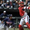 Chicago White Sox catcher Tyler Flowers, right, looks to throw to first base after forcing out Minnesota Twins\' Eduardo Escobar at home plate during the seventh inning of a baseball game in Chicago, April 21, 2013. Minnesota won 5-3. (AP Photo/Paul Beaty)