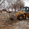 Jeff Chandler uses a front end loader to move a tree branch off of Pickard Street after a winter storm that coated trees with a thick layer of ice on Saturday, Dec. 21, 2013 in Norman, Okla. Photo by Steve Sisney, The Oklahoman
