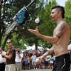 Comedian, contortionist and daredevil Al Millar, 34, juggles a small chainsaw during his high-energy performs his high-energy show Thursday during the Festival of the Arts. As the event\'s official street performer, the native Australian known as