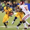 West Virginia\'s Tavon Austin (1) carries the ball as J.D. Woods (81) blocks Oklahoma\'s Aaron Colvin (15) during the fourth quarter of their NCAA college football game against Oklahoma in Morgantown, W.Va., on Saturday, Nov. 17, 2012. Oklahoma won 50-49. (AP Photo/Christopher Jackson)