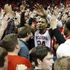 Oklahoma\'s Romero Osby (24) is surrounded by fans on the floor after the University of Oklahoma Sooners (OU) defeat the Kansas Jayhawks (KU) 72-66 in NCAA, men\'s college basketball at The Lloyd Noble Center on Saturday, Feb. 9, 2013 in Norman, Okla. Photo by Steve Sisney, The Oklahoman