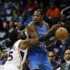 Photo - Atlanta Hawks forward DeMarre Carroll (5) reaches for the ball as he defends Oklahoma City Thunder forward Kevin Durant in the first half of an NBA basketball game Tuesday, Dec. 10, 2013, in Atlanta. (AP Photo/John Bazemore)
