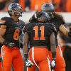From left, Oklahoma State\'s Ashton Lampkin (6), Shaun Lewis (11) and Ofa Hautau (58) celebrate a fourth-quarter interception by Lewis during a college football game between the Oklahoma State University Cowboys (OSU) and the Kansas State University Wildcats (KSU) at Boone Pickens Stadium in Stillwater, Okla., Saturday, Oct. 5, 2013. OSU won, 33-29. Photo by Nate Billings, The Oklahoman