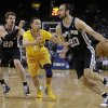 San Antonio Spurs\' Manu Ginobili, right, drives the ball against Golden State Warriors\' Stephen Curry (30) during the first half of an NBA basketball game Friday, Feb. 22, 2013, in Oakland, Calif. At left is Spurs\' Tiago Splitter (22). (AP Photo/Ben Margot)