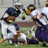 Freedom High\'s Joe Mixon (20) left, tries to get past the Amador Valley High defense before being tackled in the second quarter of their football game in Oakley, Calif., on Friday, Aug. 30, 2013. (Doug Duran/Bay Area News Group)