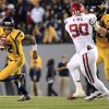 West Virginia quarterback Geno Smith (12) carries the ball as Curtis Feigt (62) blocks Oklahoma\'s David King (90) during the fourth quarter of their NCAA college football game against Oklahoma in Morgantown, W.Va., on Saturday, Nov. 17, 2012. Oklahoma won 50-49. (AP Photo/Christopher Jackson)