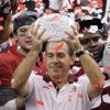 FILE- In this Jan. 9, 2012, file photo, Alabama head coach Nick Saban holds up the trophy as he celebrates with his team after defeating LSU 21-0 in the BCS national championship NCAA college football game in New Orleans. The D word - as in dynasty - is off-limits around Alabama. But if Saban\'s Crimson Tide can beat No. 1 Notre Dame to become the first team to win consecutive BCS championships and three national titles in four years, Alabama will lay claim to one of the sport\'s great runs. (AP Photo/Gerald Herbert, File) ORG XMIT: NY162