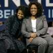 FILE - In this Dec. 9, 2007 file photo, Michelle Obama, left, wife of Democratic presidential hopeful Sen. Barack Obama, D-Ill. and Oprah Winfrey sit together during a rally in Manchester, N.H. Sunday, Dec. 9, 2007. The nationÂ's first lady turns 50 on Friday and, by her own account, feels more relaxed now that President Barack ObamaÂ's days as a candidate for elected office are over.  (AP Photo/Elise Amendola)