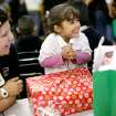 With kindergarten teacher Tina Winkle watching (left) Itzel Chavez, a kindergarten student at Santa Fe South, reacts as she sees her gift during the annual Christmas Party and gift exchange at Santa Fe South High School in OKlahoma City on Friday, Dec. 3, 2010. Photo by John Clanton, The Oklahoman