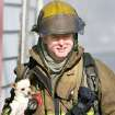 DOG: Oklahoma City firefighter C.J. Seitz carries a chihuahua from a house fire in the 2400 block of NW 2nd in Oklahoma City, Okla. Monday, December 29, 2008.  BY STEVE GOOCH, THE  OKLAHOMAN.  ORG XMIT: KOD