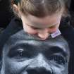 Lillian Dowe, 8, looks at a T-shirt with the image of Rev. Martin Luther King Jr. on it during the Black Heritage Society's 36th Annual Original Martin Luther King Jr. Parade in downtown Houston, Monday, Jan. 20, 2014. (AP Photo/Houston Chronicle, Johnny Hanson)