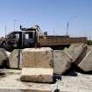 This photo taken on Tuesday, July 1, 2014, shows a damaged military truck after clashes between fighters of the al-Qaida-inspired Islamic State of Iraq and the Levant (ISIL) and Iraqi security forces at a military base in Tikrit, 80 miles (130 kilometers) north of Baghdad, Iraq. The Islamic State of Iraq and the Levant announced this week that it has unilaterally established a caliphate in the areas under its control. It declared the group's leader, Abu Bakr al-Baghdadi, the head of its new self-styled state governed by Shariah law and demanded that all Muslims pledge allegiance to him. (AP Photo)