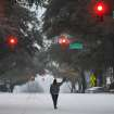 A man waves while walking along the center of Clayton Street on Wednesday, Feb. 12, 2014, in Athens, Ga. A combination of sleet, snow and freezing rain was expected to coat power lines and tree branches with more than an inch of ice between Atlanta and Augusta. (AP Photo/Athens Banner-Herald, AJ Reynolds)  MAGS OUT; TV OUT: MANDATORY CREDIT
