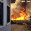 In this still frame from video provided by KNSD-TV, flames near a home as crews scrambled to corral a wildfire that burned two homes near the San Diego County mountain town of Julian in Southern California Thursday, July 3, 2014. The blaze erupted around 10:30 a.m. and prompted the mandatory evacuation of 200 homes. Firefighters attacked the 150-acre blaze in the air and on the ground. The fire destroyed two homes and an outbuilding and was 15 percent contained at nightfall, state fire Capt. Kendal Bortisser said. (AP Photo/KNSD-TV)