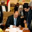 In this photo provided by Yemen's Defense Ministry, Yemeni President Abed Rabbo Mansour Hadi signs the final approval on transforming Yemen into a federal state of six regions in Sanaa Yemen, Monday, Feb. 10, 2014. A key Yemeni panel tasked with devising a new system to address the local grievances that have fed the impoverished Arabian Peninsula nation's instability agreed Monday to transform the country into a state of six regions. (AP Photo/Yemen's Defense Ministry)
