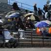 Fans sit under umbrellas as rain begins to fall during Putnam City - Broken Arrow high school football game at Putnam City Stadium Friday night. PHOTO BY HUGH SCOTT FOR THE OKLAHOMAN ORG XMIT: KOD
