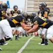 In this 2012 photo provided by Adrian College, members of the school's Bulldog football team warm up before homecoming in Adrian, Mich. Adrian's president, Jeffrey Docking, has added seven sports and two pre-professional degree programs to the liberal arts college since arriving in 2005 _ and nearly doubled enrollment to about 1,750. (AP Photo/Adrian College, Matt Gaidica Photography)