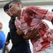 An injured prison inmate is escorted by a policeman into the hospital in Barquisimeto, Venezuela,  Friday, Jan. 25, 2013. A bloody riot erupted at the Uribana prison in the central Venezuelan city of Barquisimeto Friday when National Guard troops clashed with inmates, and Venezuelan media reported that dozens were killed. It was the latest in a series of bloody riots in the countrie's prisons.(AP Photo/Rafael Rodriguez/El Informador)