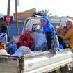 Local people travel on the back of a truck in Tel Abyad, Syria, Friday, Oct. 5, 2012. On Friday, a Syrian mortar round hit inside Turkey, causing no injuries, and Turkish troops returned fire, the state-run news agency Anadolu said late Friday, and Turkey deployed more troops near to the border with Syria. (AP Photo)